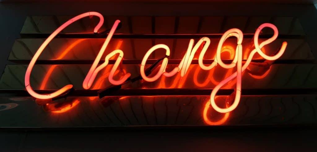 """the word """"change"""" written in orange neaon lights on dark background"""