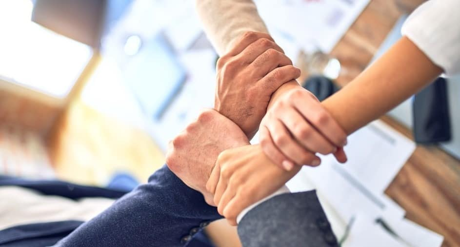 4 co-workers clasping wrists in unity