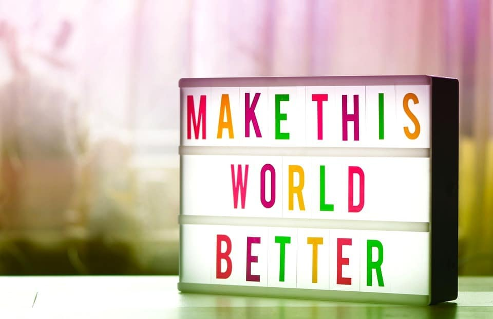 colorful letters on a lightboard spelling out make this world a better place