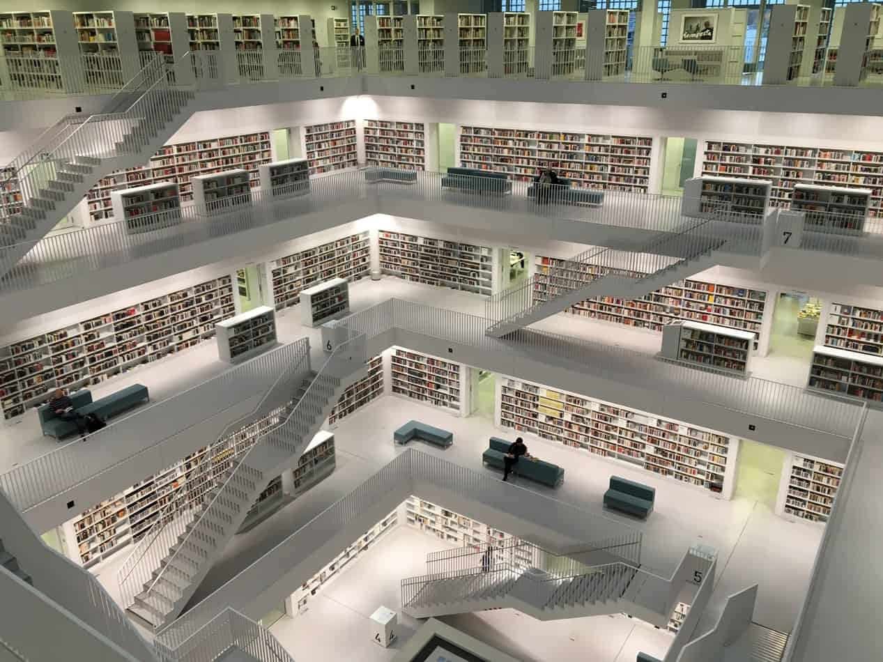 person sitting in a multi floor modern library